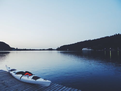 White Kayak on Brown Wooden Dock