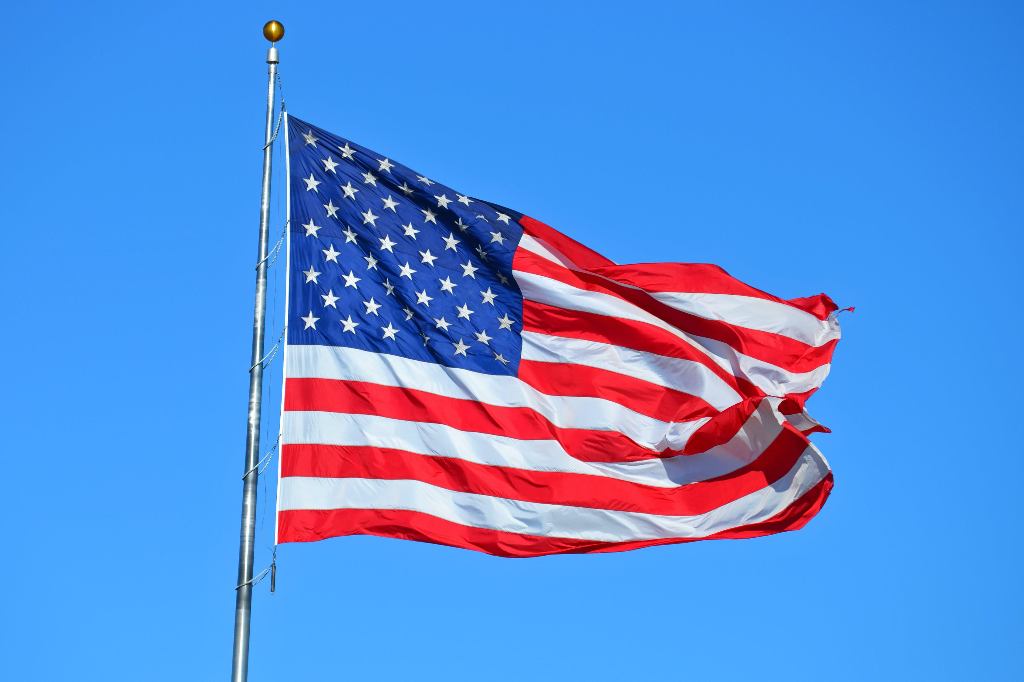 The US Flag flying in front of the bright blue sky