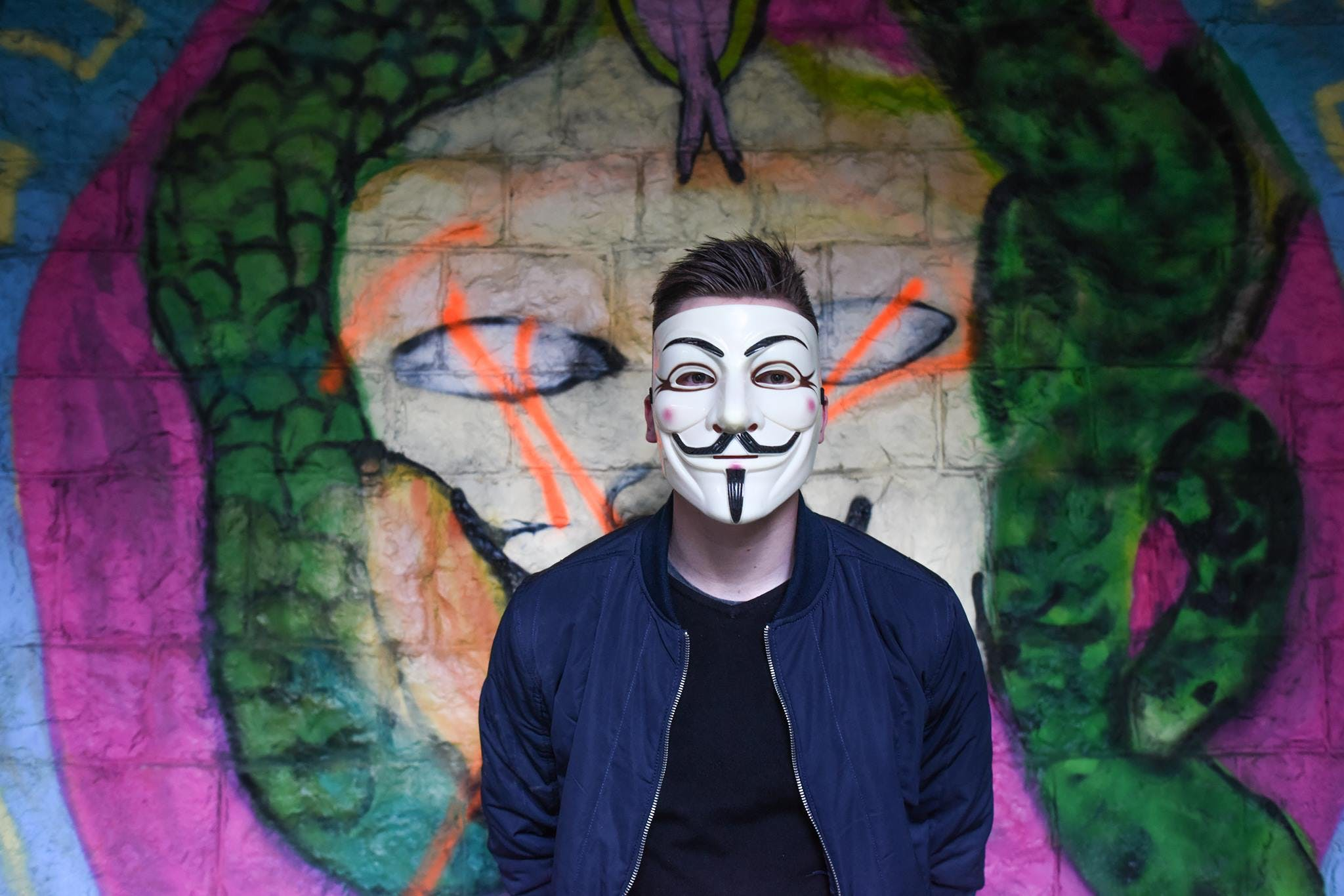 Man in White Mask in Black Crew Neck Shirt and Blue Zip Up Jacket Infront Graffiti Wall