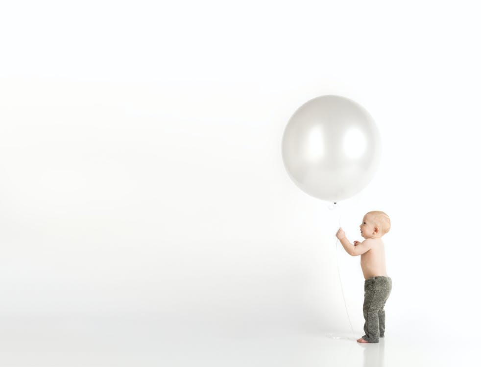 Baby in Black Pants Holding White Balloon While Standing