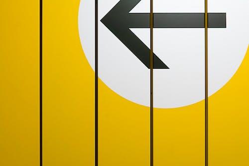 Black Arrow on Yellow Wall