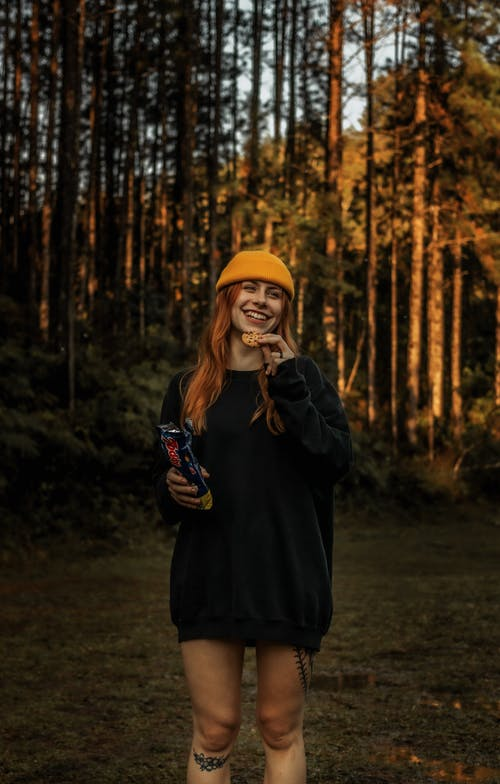 Woman in Black Coat and Yellow Knit Cap Standing in Forest
