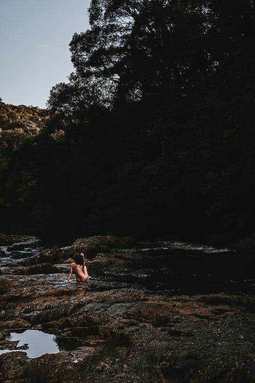 Woman in White Bikini Sitting on Brown Rock Near Green Trees