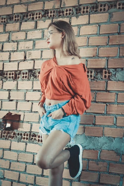 Woman Wearing Brown Long-sleeved Blouse and Blue Denim Short Shorts Standing Behind Brown Brick Wall