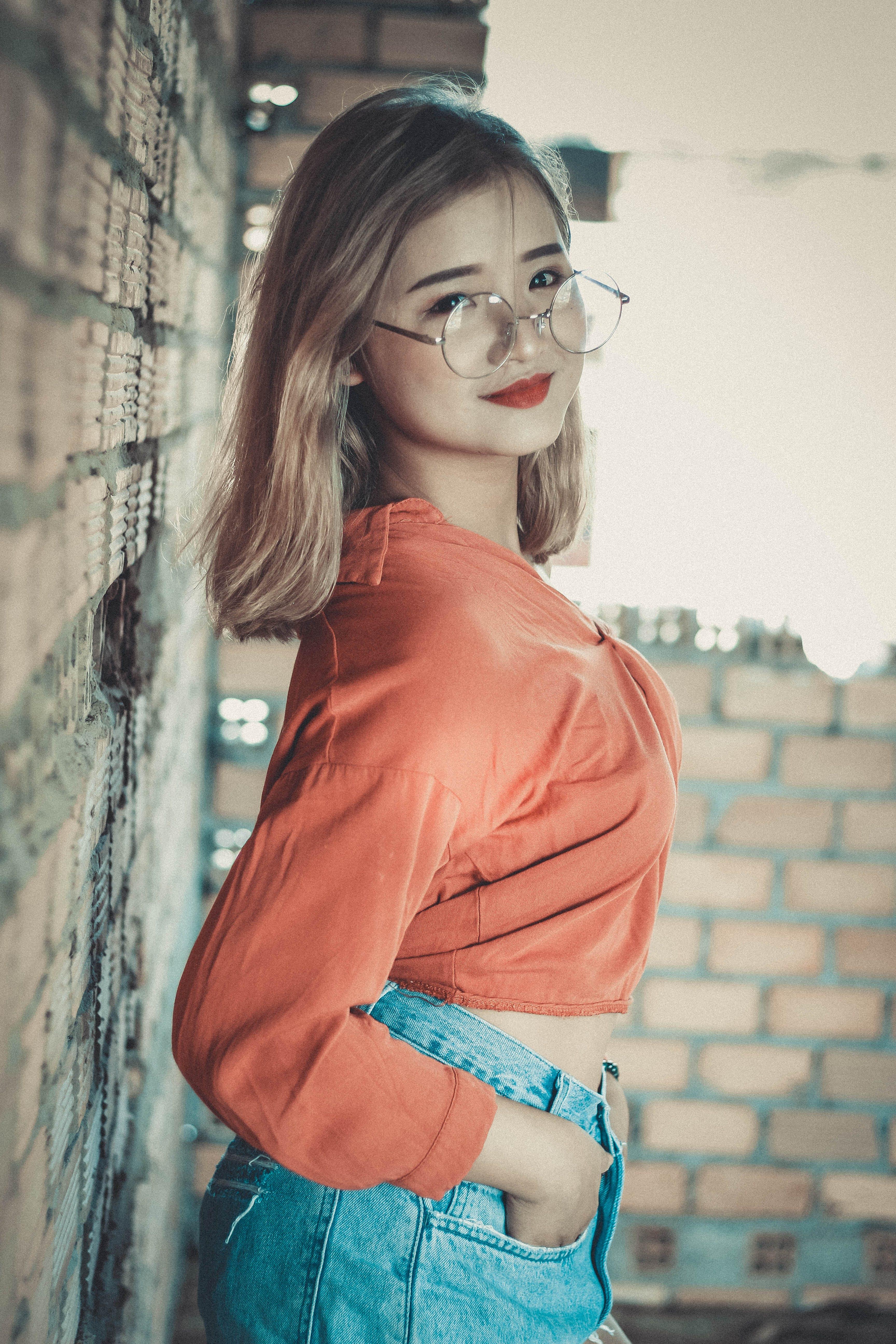 Blonde Haired Woman in Orange Long-sleeved Crop Top Wearing Round Gray Eyeglasses