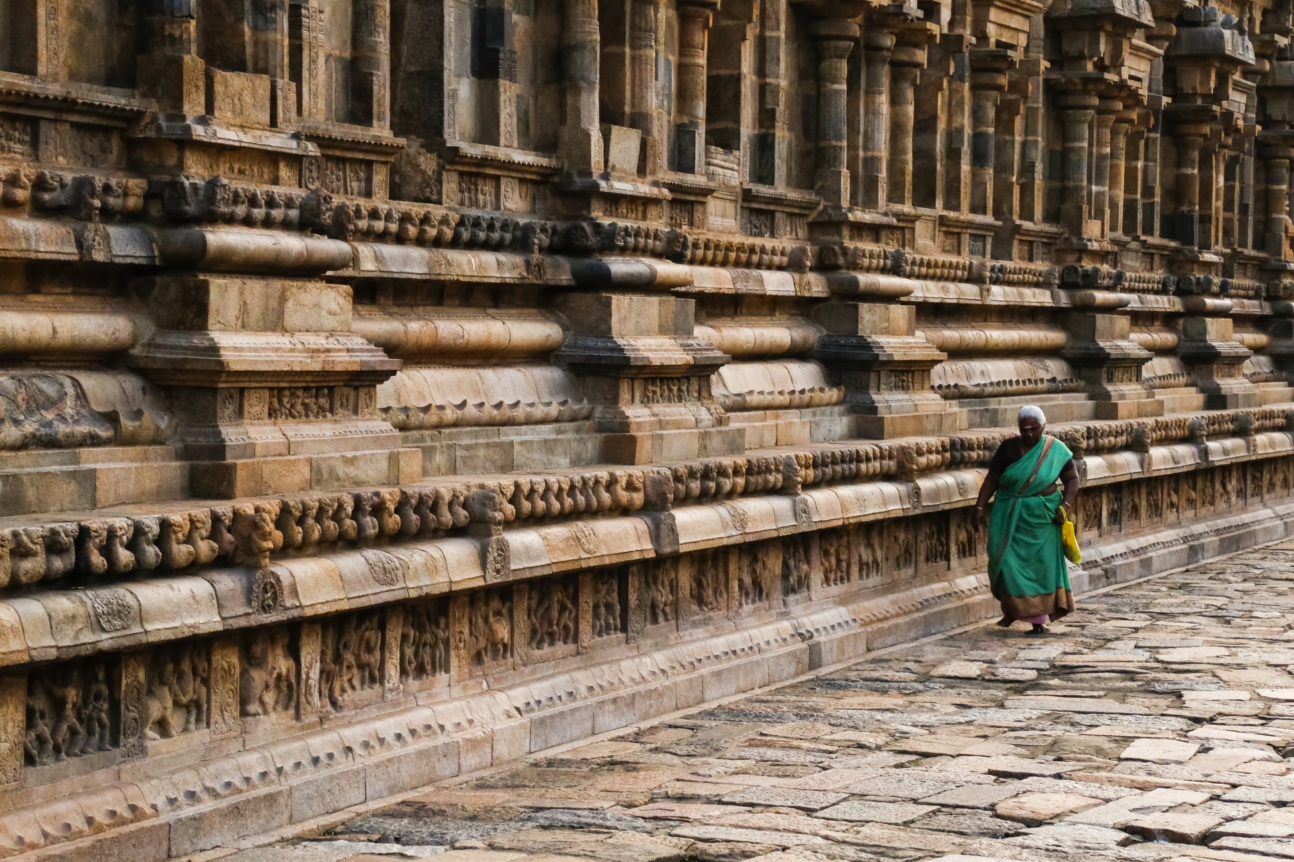 Photo of Woman Wearing Teal Traditional Dress Walking Along Pavement