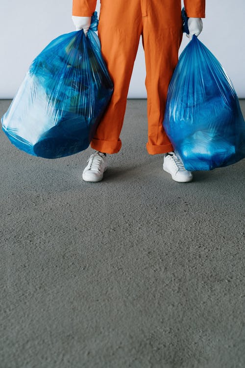 Hands Holding Blue Garbage Bags