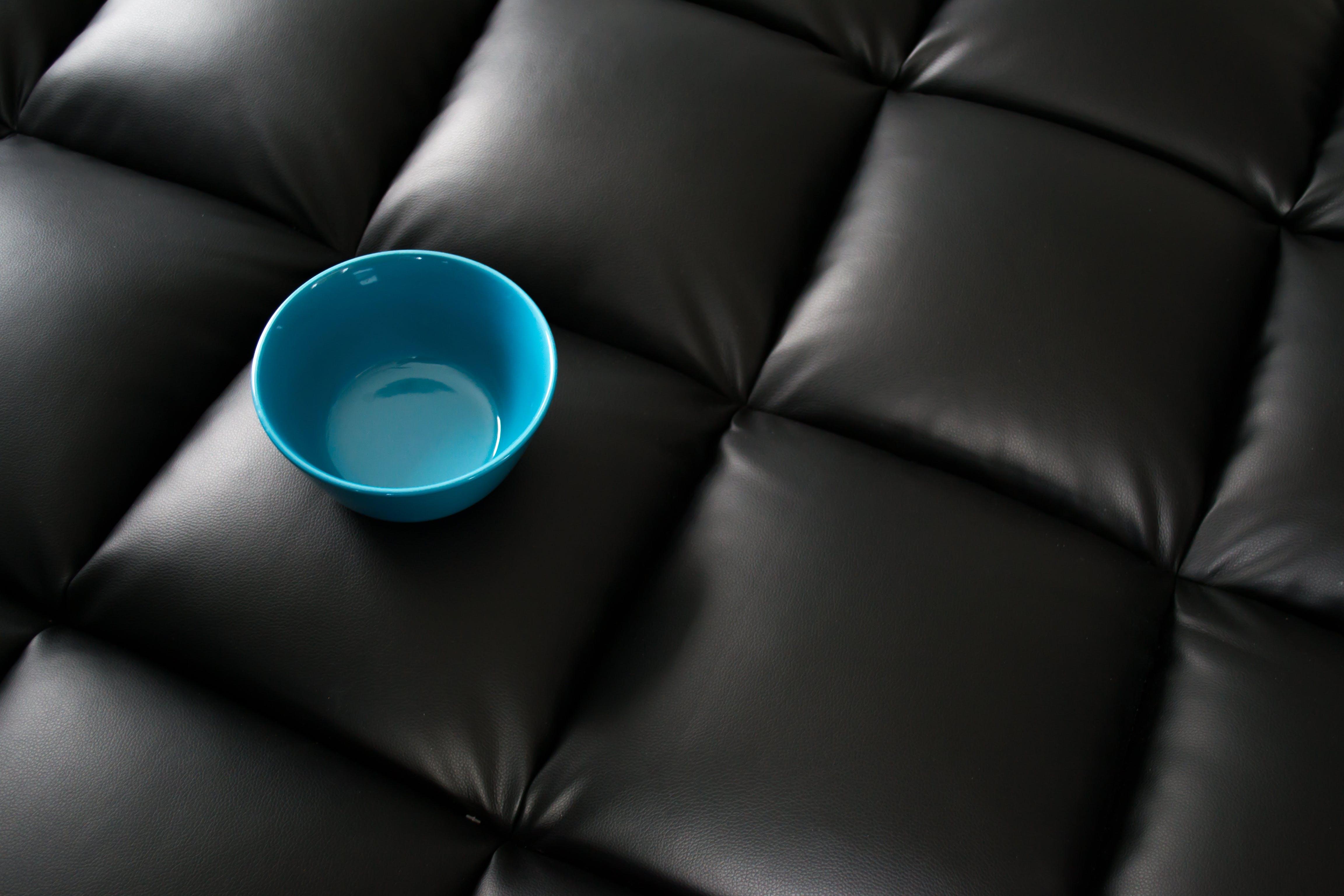 Blue Ceramic Bowl on Black Leather Surface
