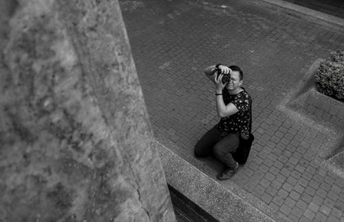 Grayscale Photography of Man Taking Picture