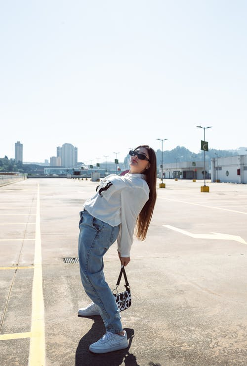 Woman in White Long Sleeve Shirt and Blue Denim Jeans Standing on Gray Concrete Road during