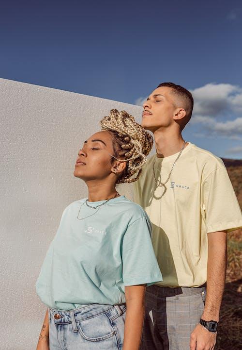 Man in White Crew Neck T-shirt Standing Beside Woman in White Crew Neck T-shirt