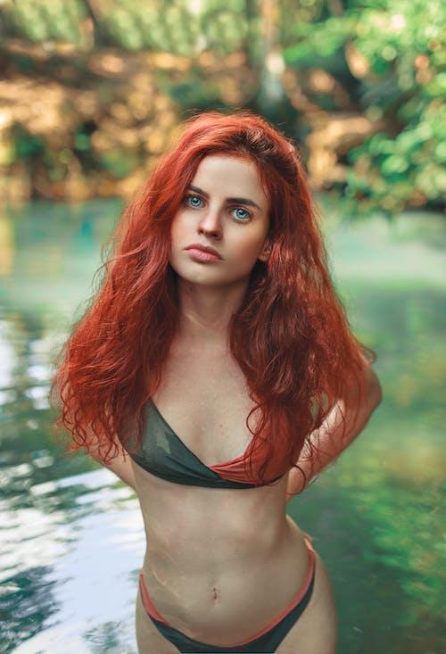 Woman in Black Bikini Top Standing on Water