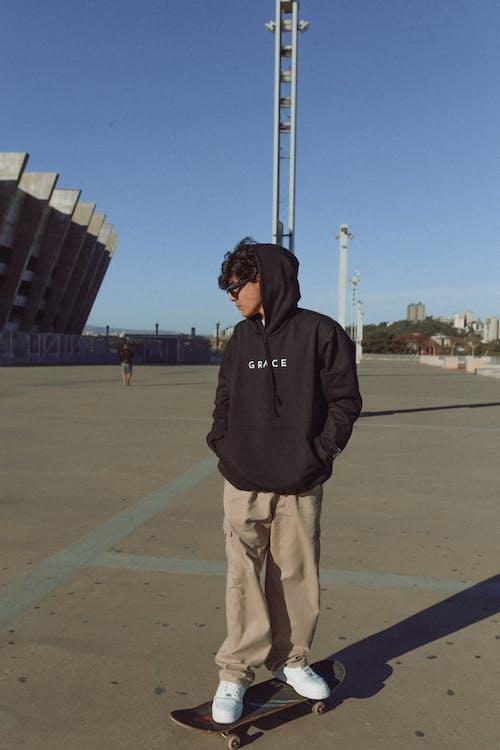 Man in Black Hoodie Standing on Brown Field