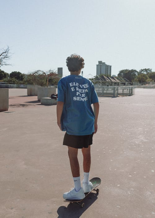 Man in Blue Crew Neck T-shirt and Black Shorts Standing on Brown Sand