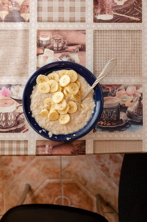 Oatmeal with Slices of Bananas in Blue Ceramic Bowl