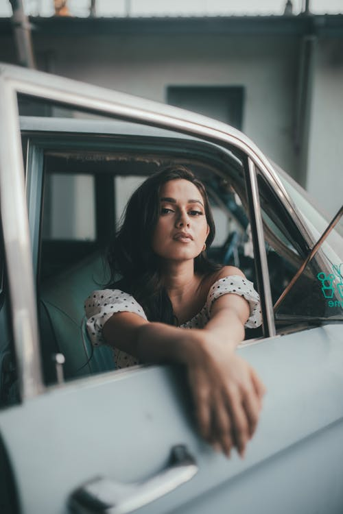 Woman in White Shirt Leaning on White Car