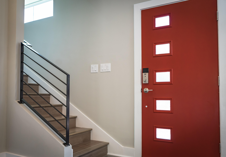 Red wooden door beside the stairs.   Photo: Pexels