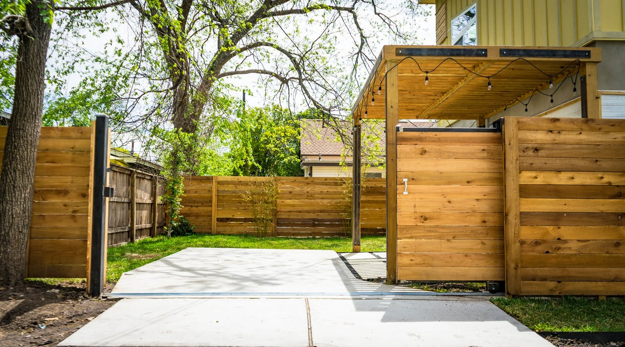 Photo of Opened Brown Wooden Sliding House Gate