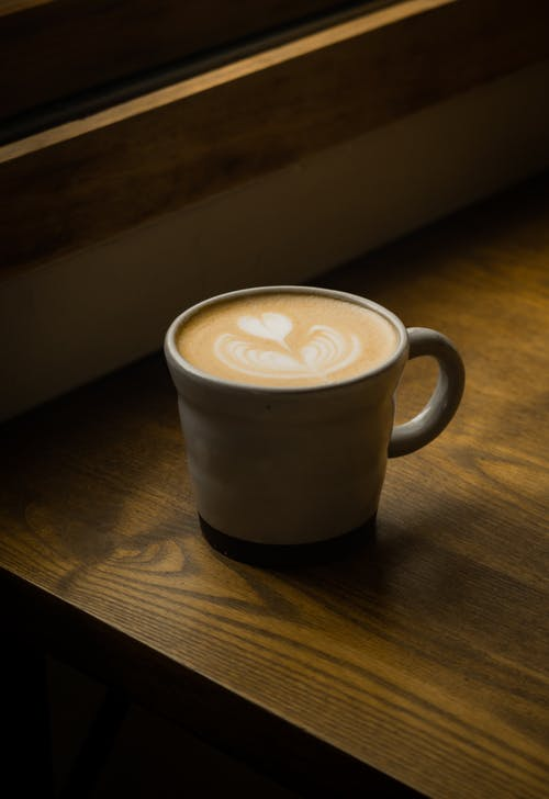 Close-Up Shot of a Cup of Cappuccino on a Wooden Table