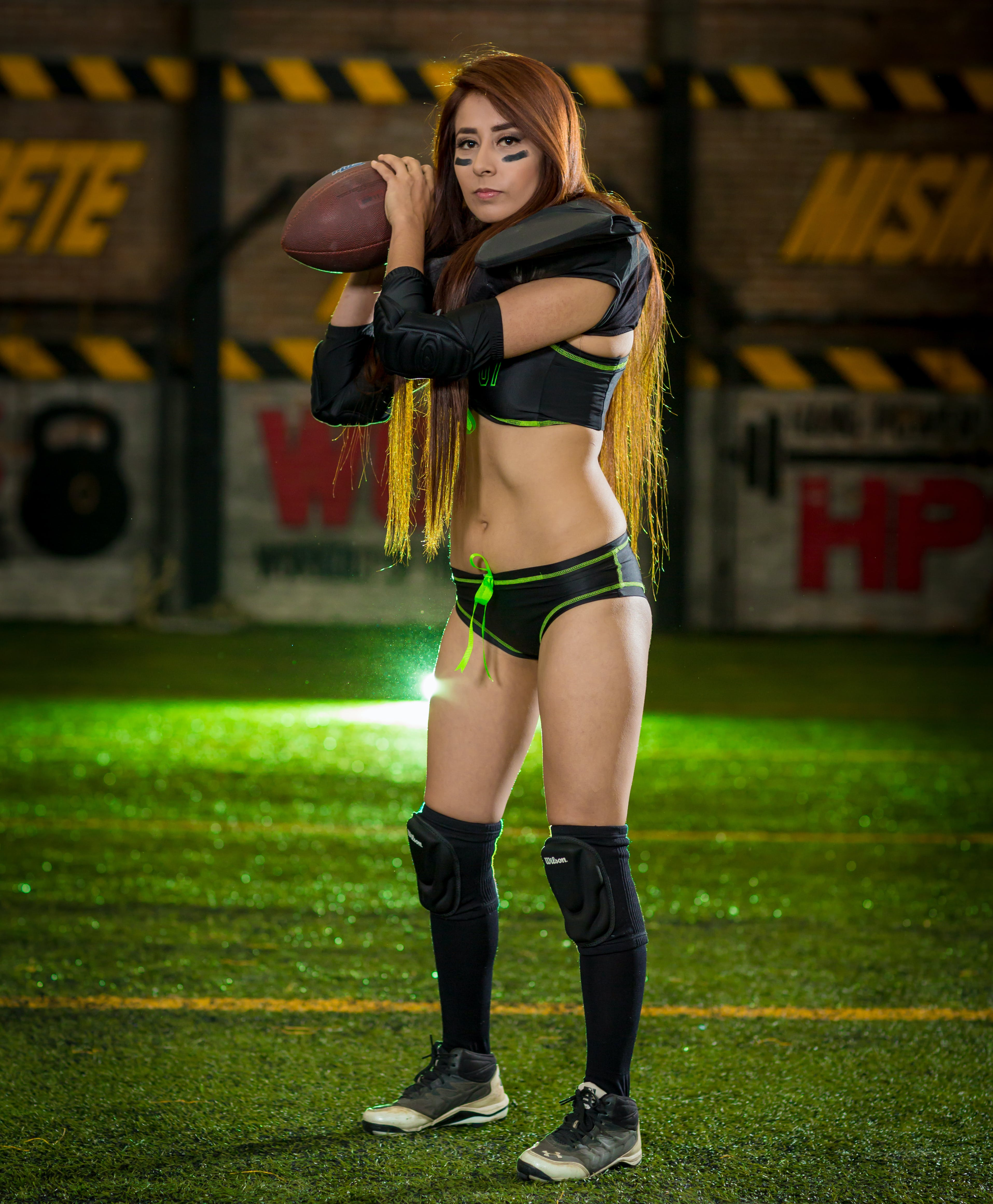Woman Wearing Black-and-green Sports Bra and Pantie Holding Rugby Ball