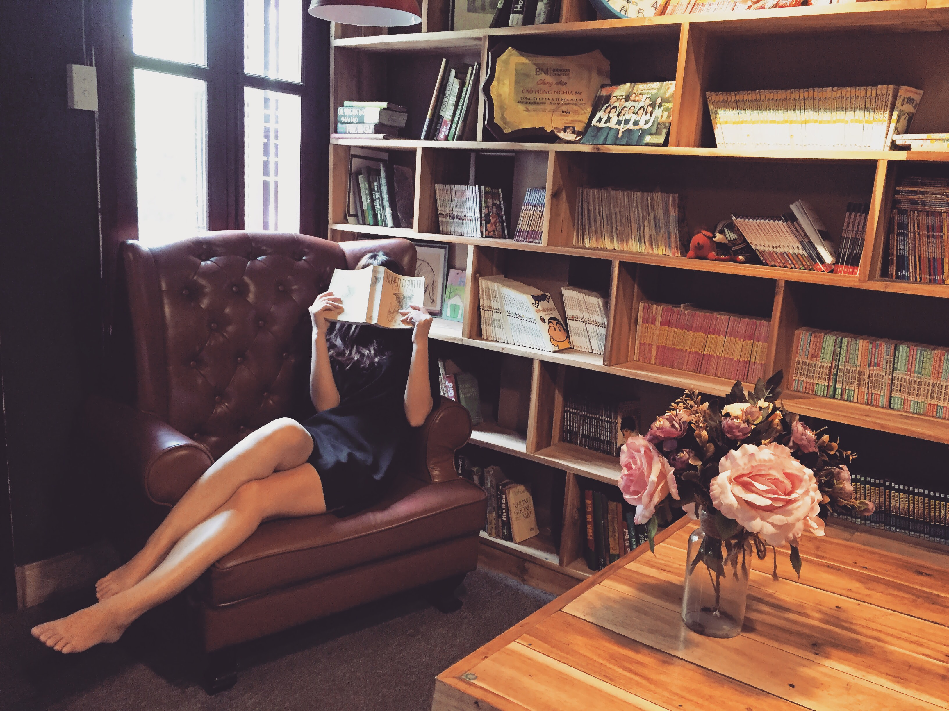Woman In Black Mini Dress Sitting On Brown Leather Tufted Sofa Chair