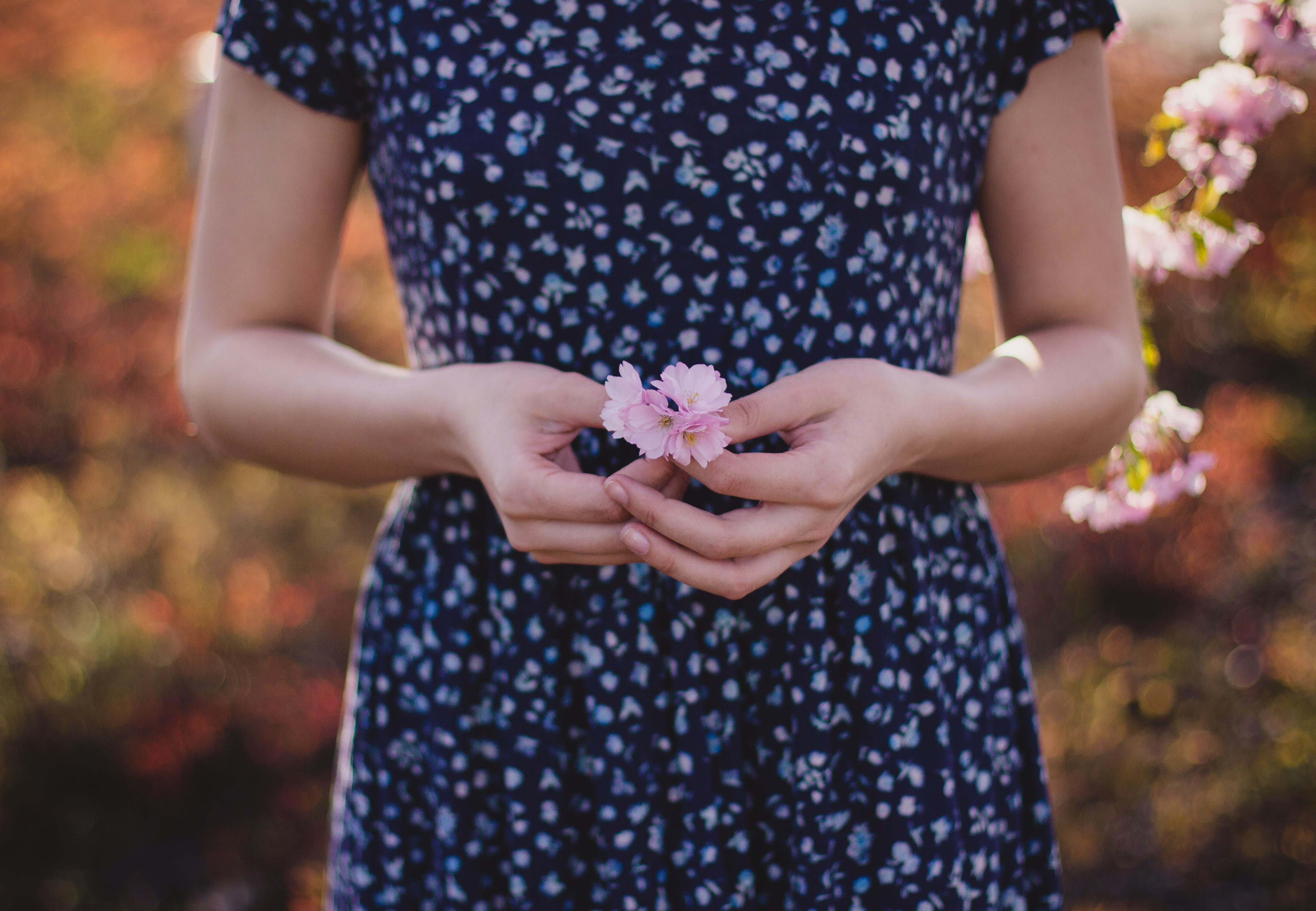 Women in Blue and White Floral Dress With Pink Flower on Hand