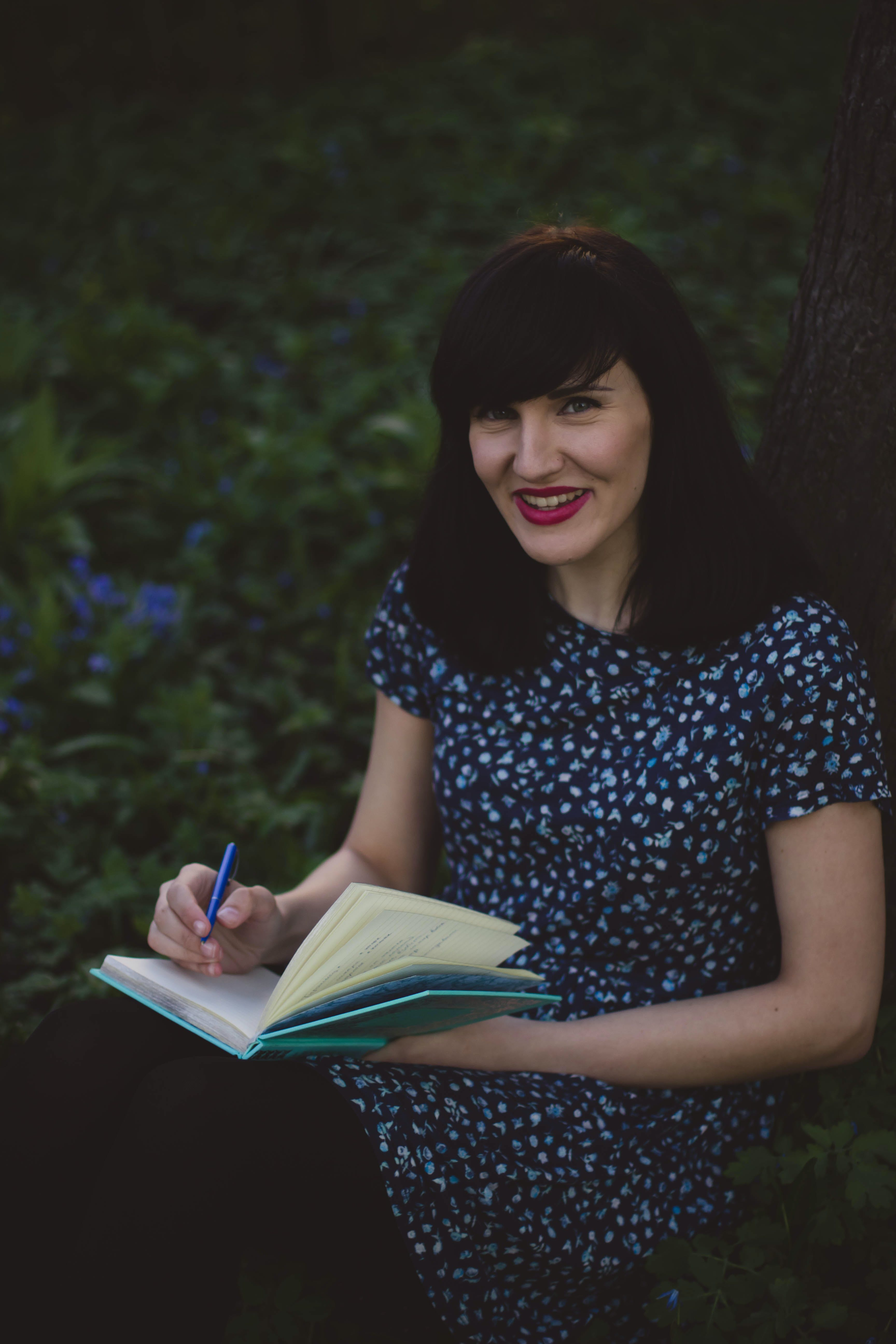 Woman in White and Blue Floral Crew Neck Short Sleeve Shirt Holding a Teal Notebook Leaning in Brown Tree Trunks