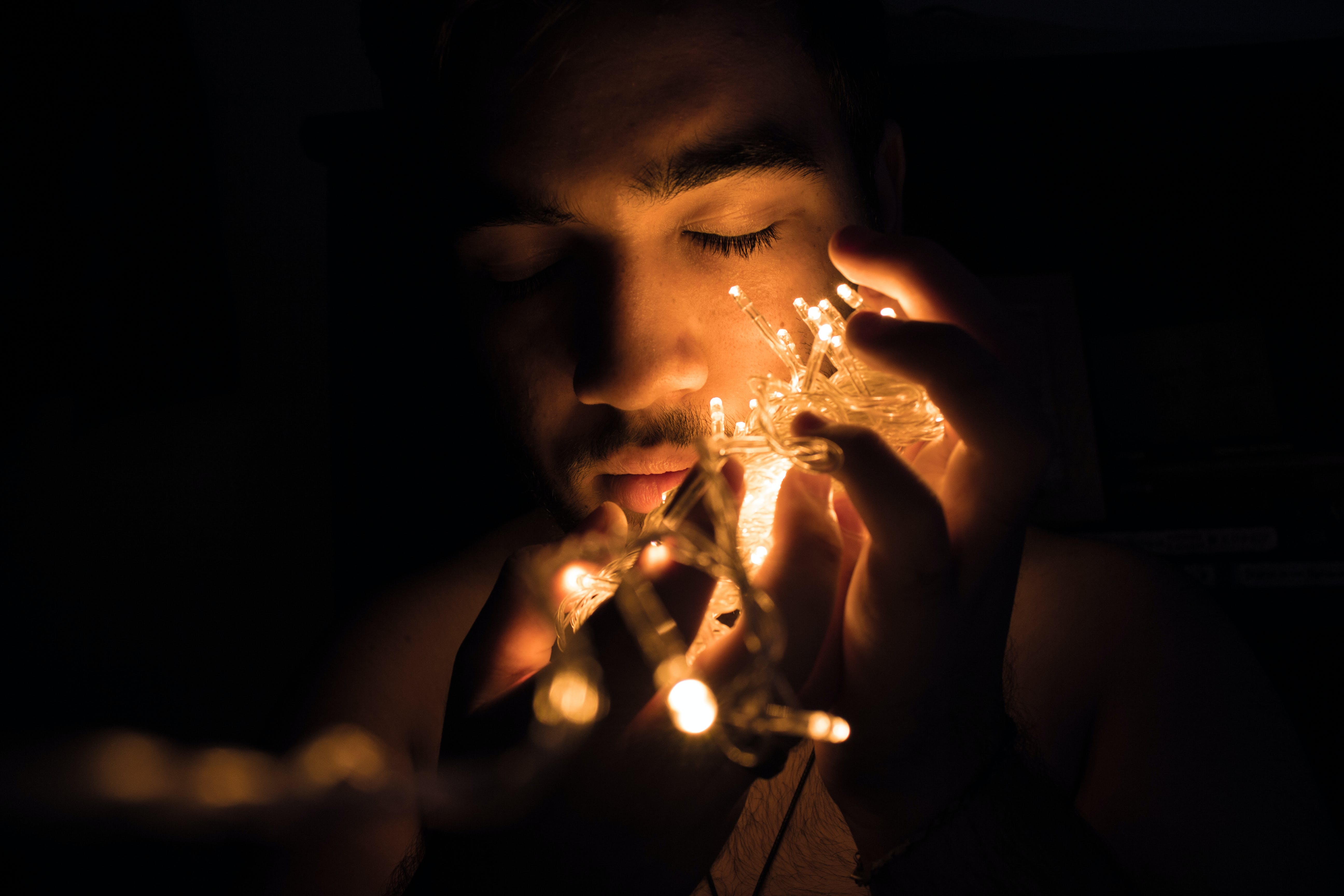 Close-up Photography of Man Holding Christmas Lights