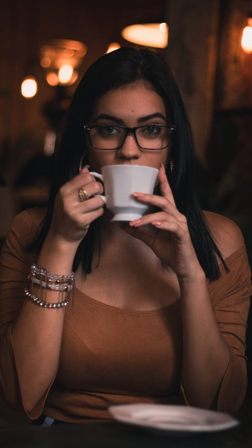 Woman Wearing Brown Scoop-neck Quarter-sleeved Top Holding White Ceramic Mug
