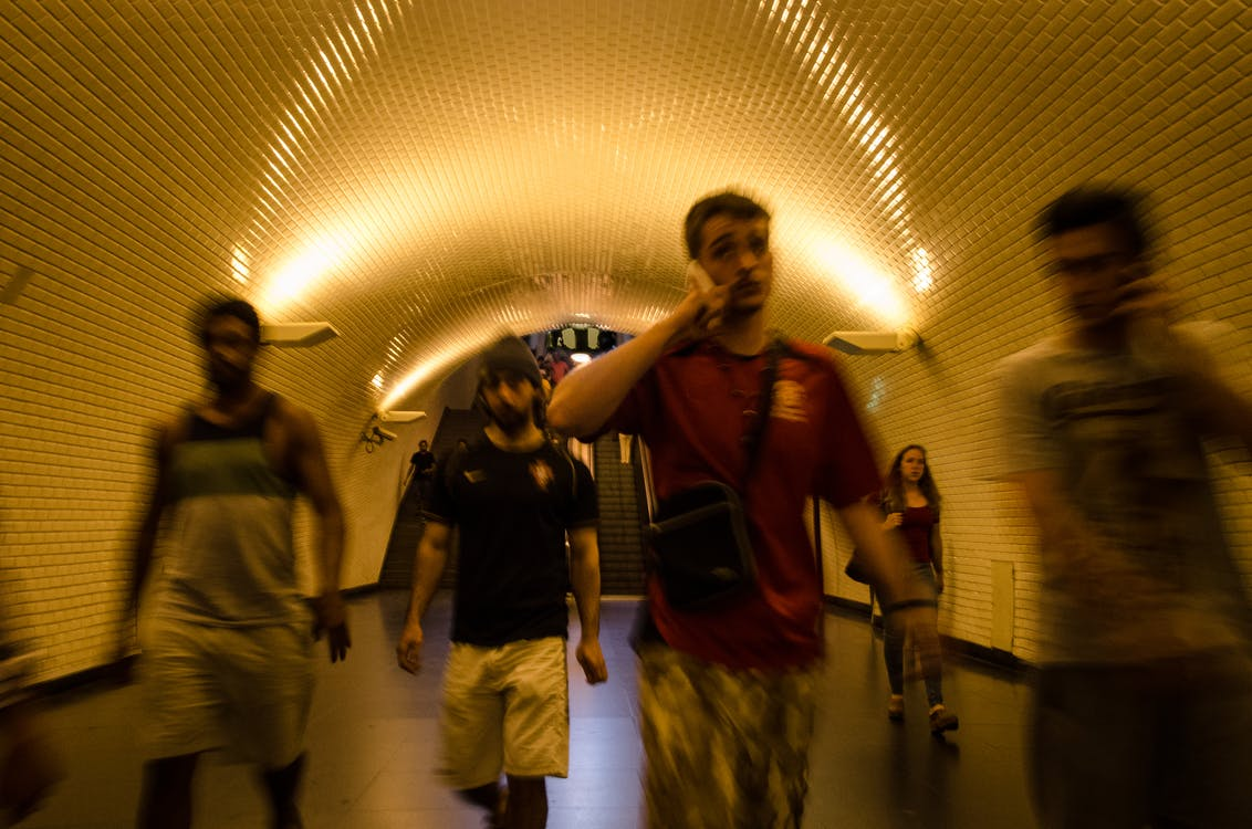 People Walking Inside Tunnel Pathway