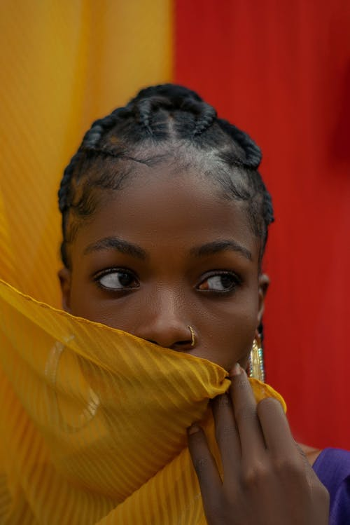 A Woman Covering Her Face With A Yellow Cloth