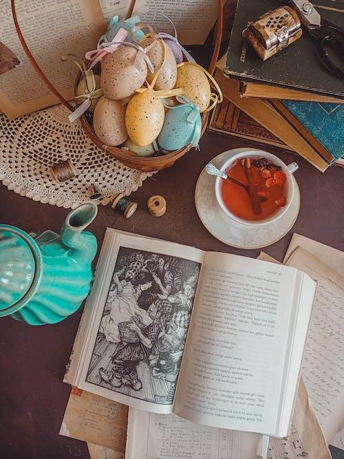 An Open Book in Between a Tea Pot And a Tea Cup