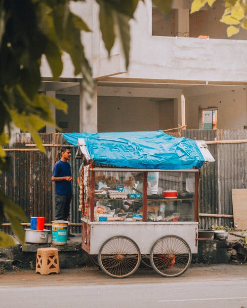 Blue and White Food Cart Near White Concrete Building