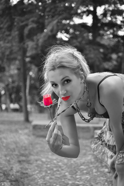 Selective Color Photo of Woman Holding Rose
