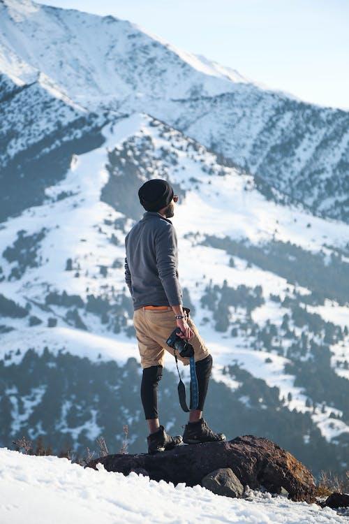 Man Wearing Gray Long-sleeved Shirt and Brown Shorts Holding Black Dslr Camera on Mountain