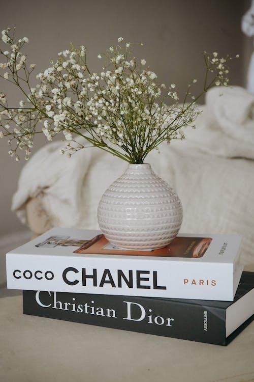 White Flowers in White Ceramic Vase on Top of Books