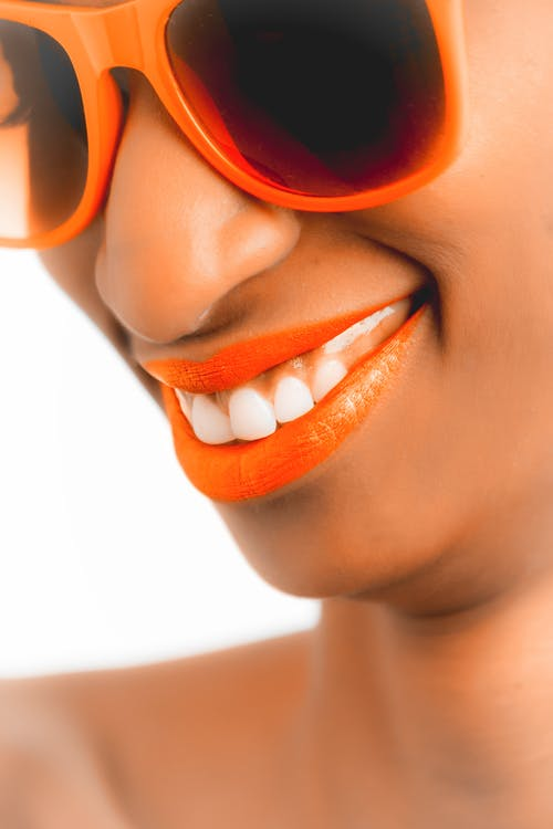 Woman Wearing Orange Frame Sunglasses and Orange Lipstick