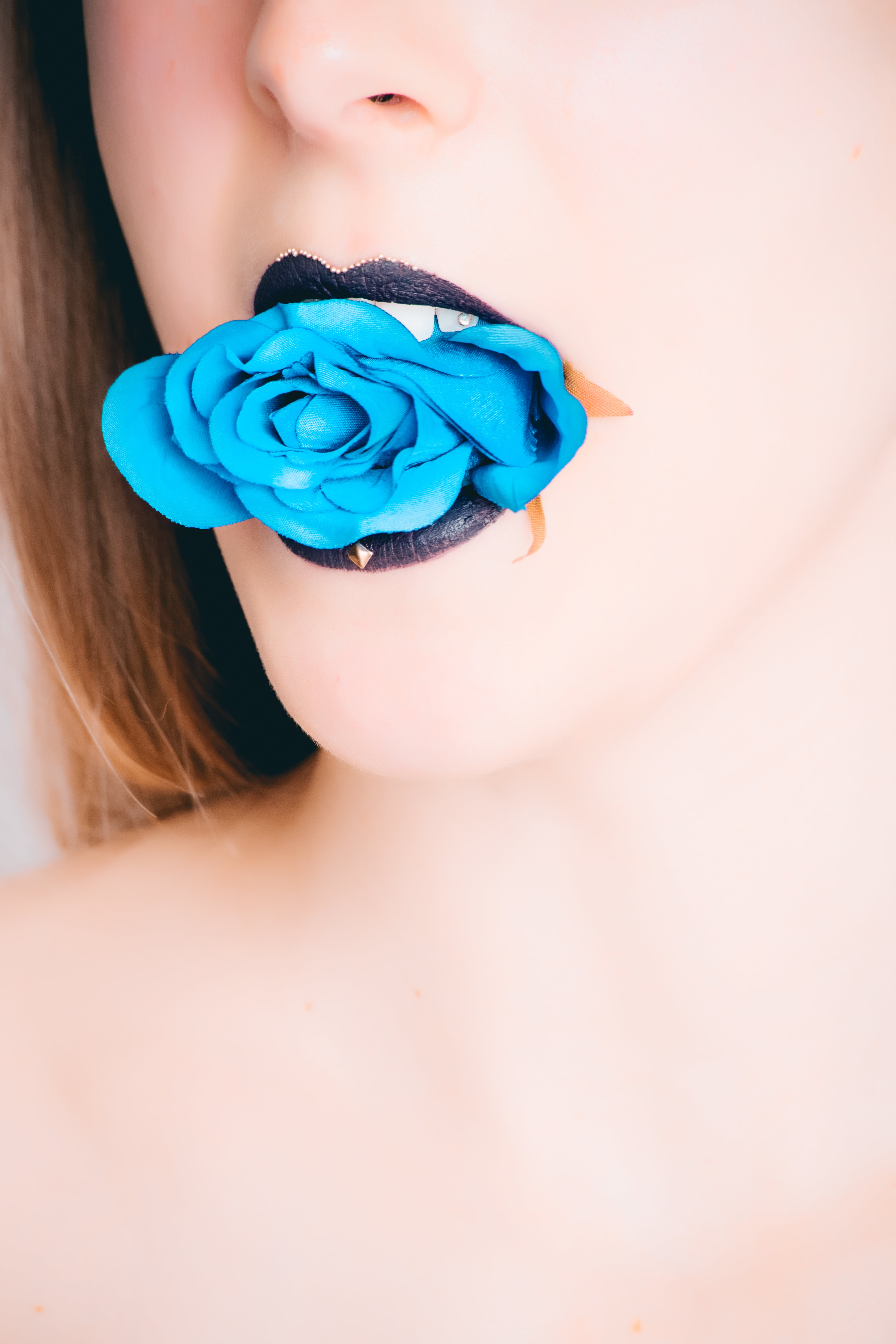 Woman With Black Lipstick Biting Blue Rose