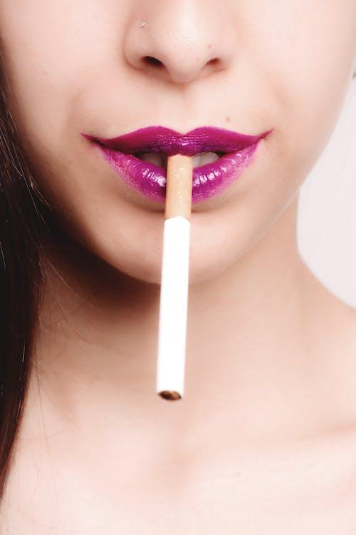 White Cigarette Stick on Woman's Mouth