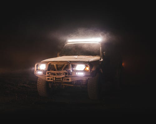 Brown Car on Black Field during Night Time