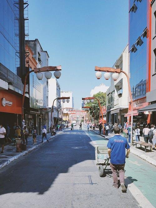 Man in Blue Jacket and Black Pants Walking on Sidewalk