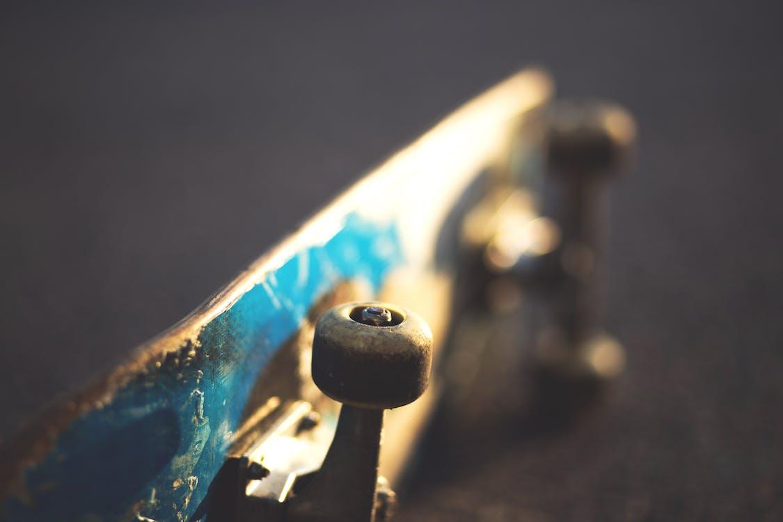 Blue and White Skateboard on Concrete Floor Slightly Tilted