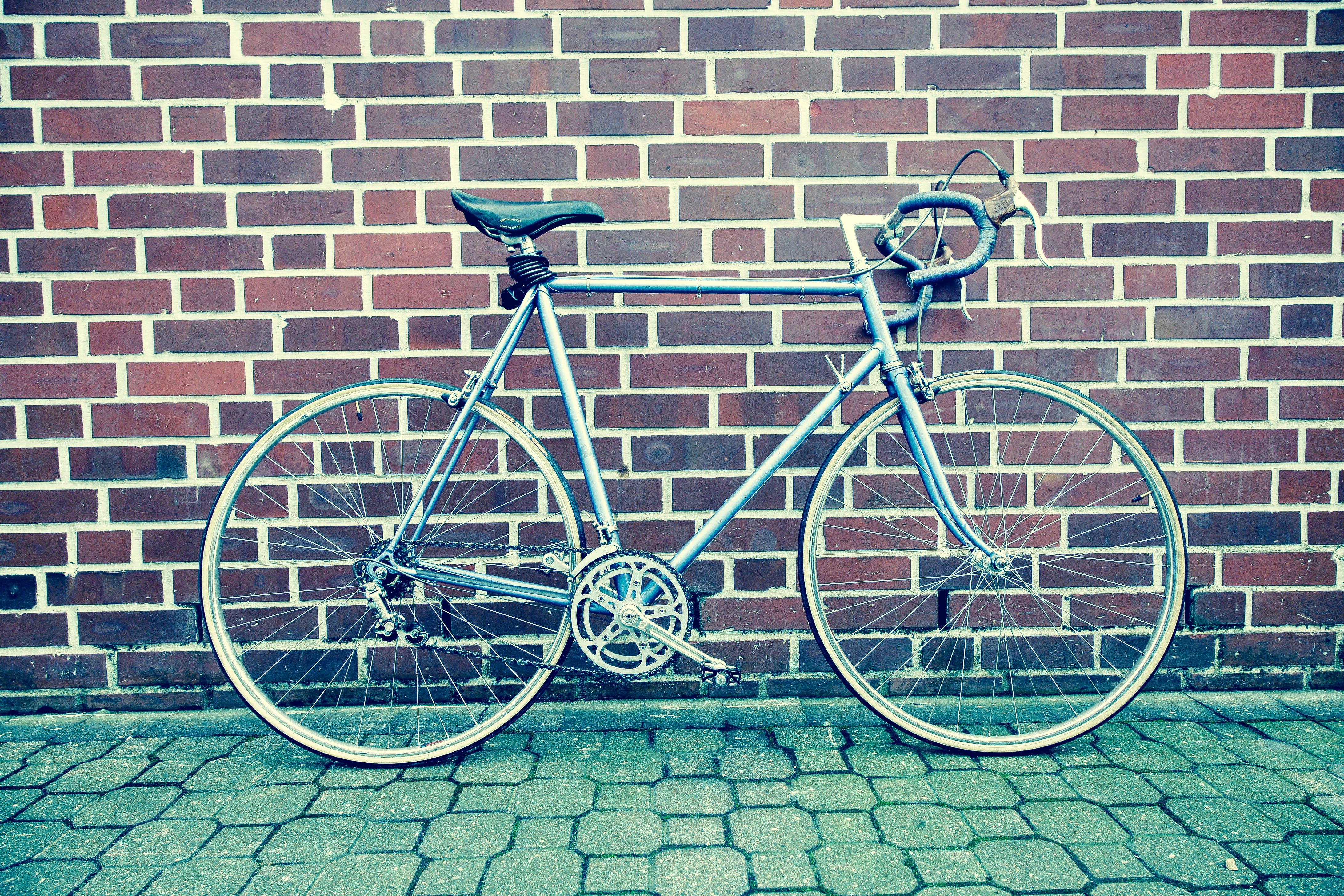 Teal and Black Road Bike Near Black and Brown Brick Wall