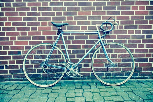 Teal and Black Road Bike Near Black and Brown Brick Wall