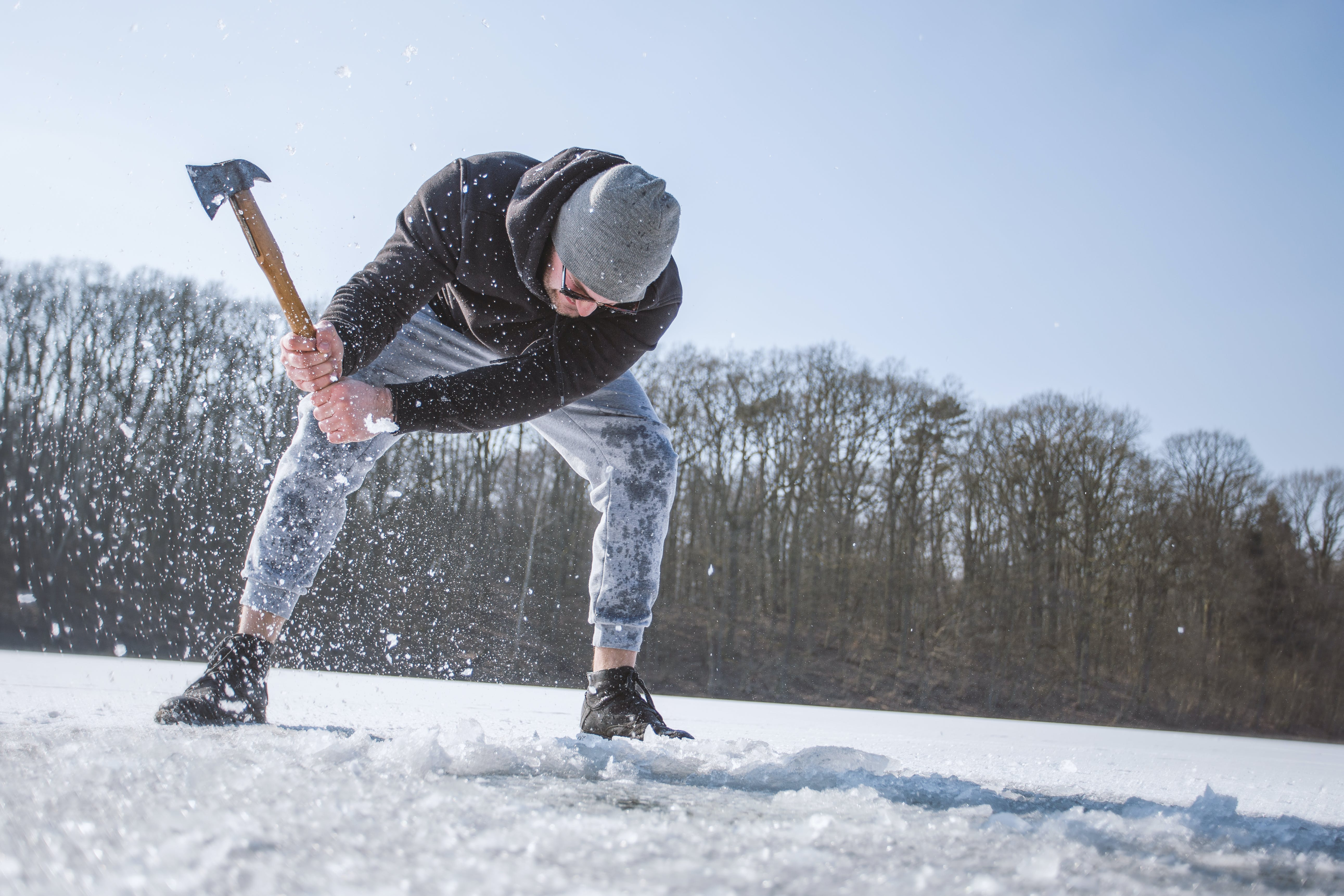 Man Wearing Black Hooded Jacket, Gray Knit Cap, Gray Pants, and Black Shoes Holding Brown Handled Axe While Bending on Snow