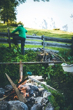 Man in Green Hoodie and Black Pants Climbing on Fence