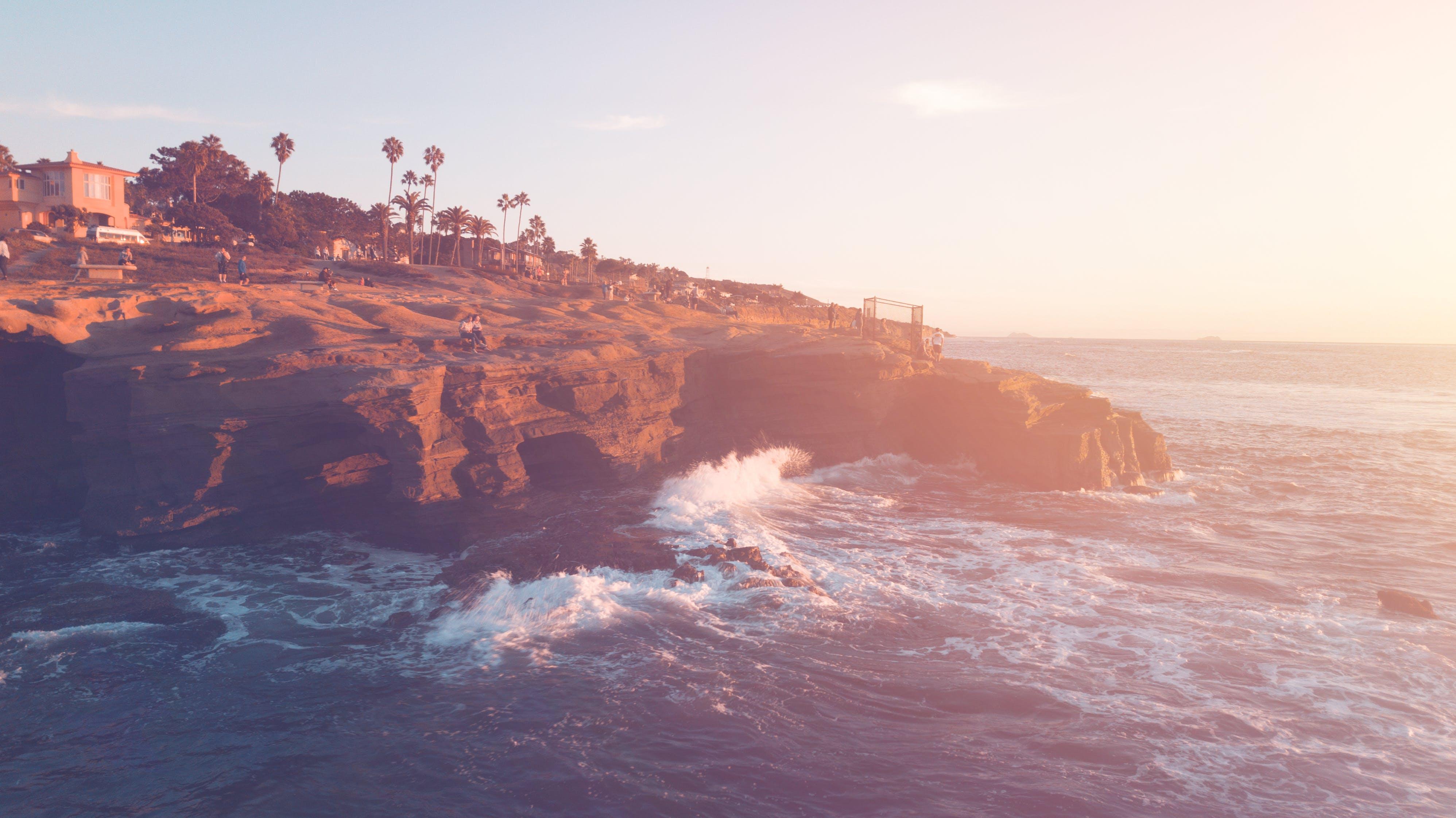 Brown Cliff Beside Ocean Under Blue Sky