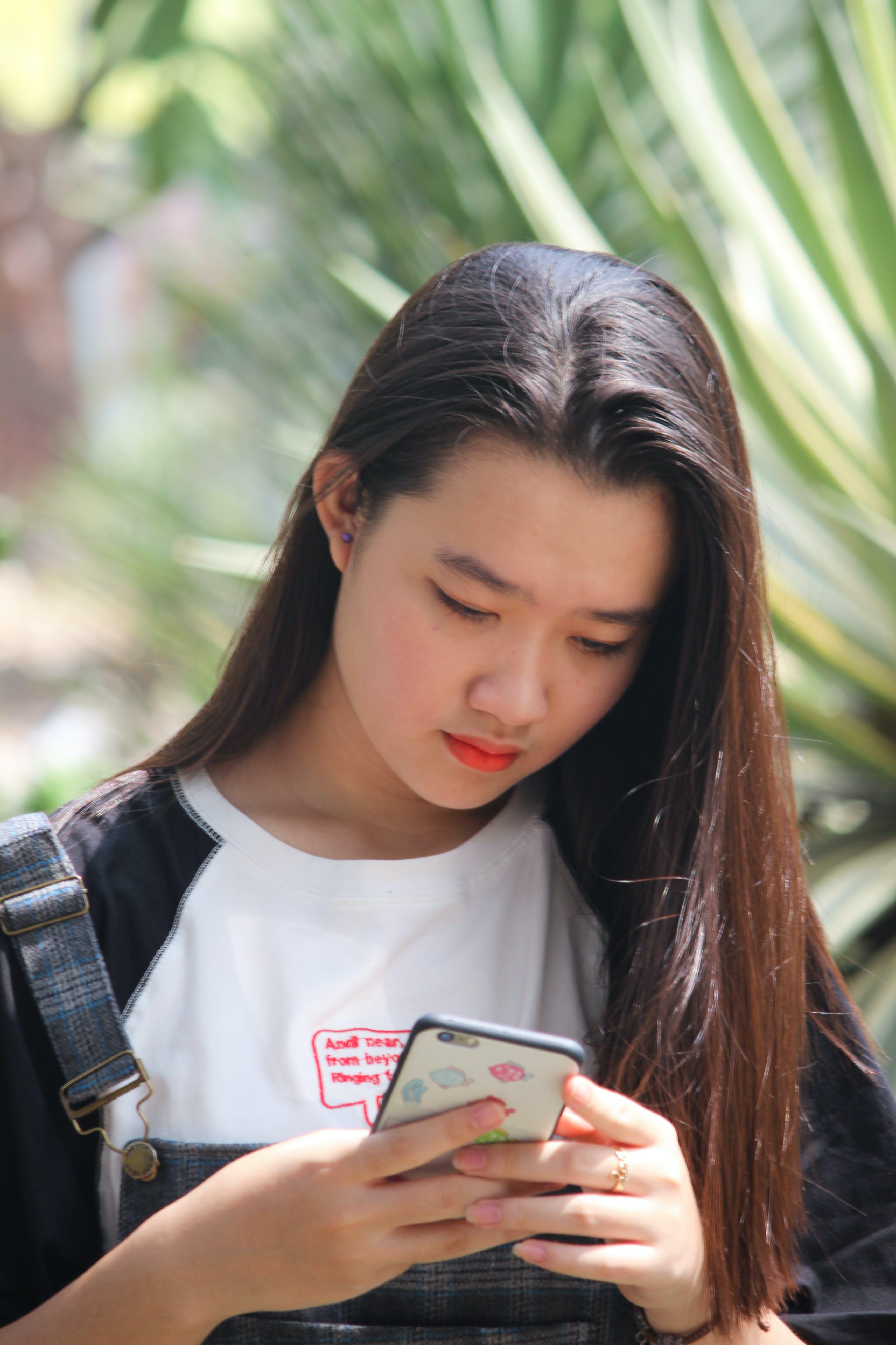 Woman Using Phone Standing Near Leaf