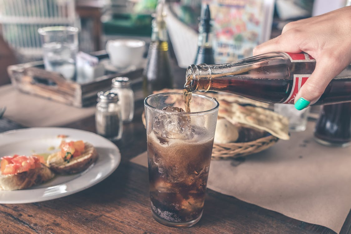 Photo of Cola Pouring Into a Glass with Ice Cubes