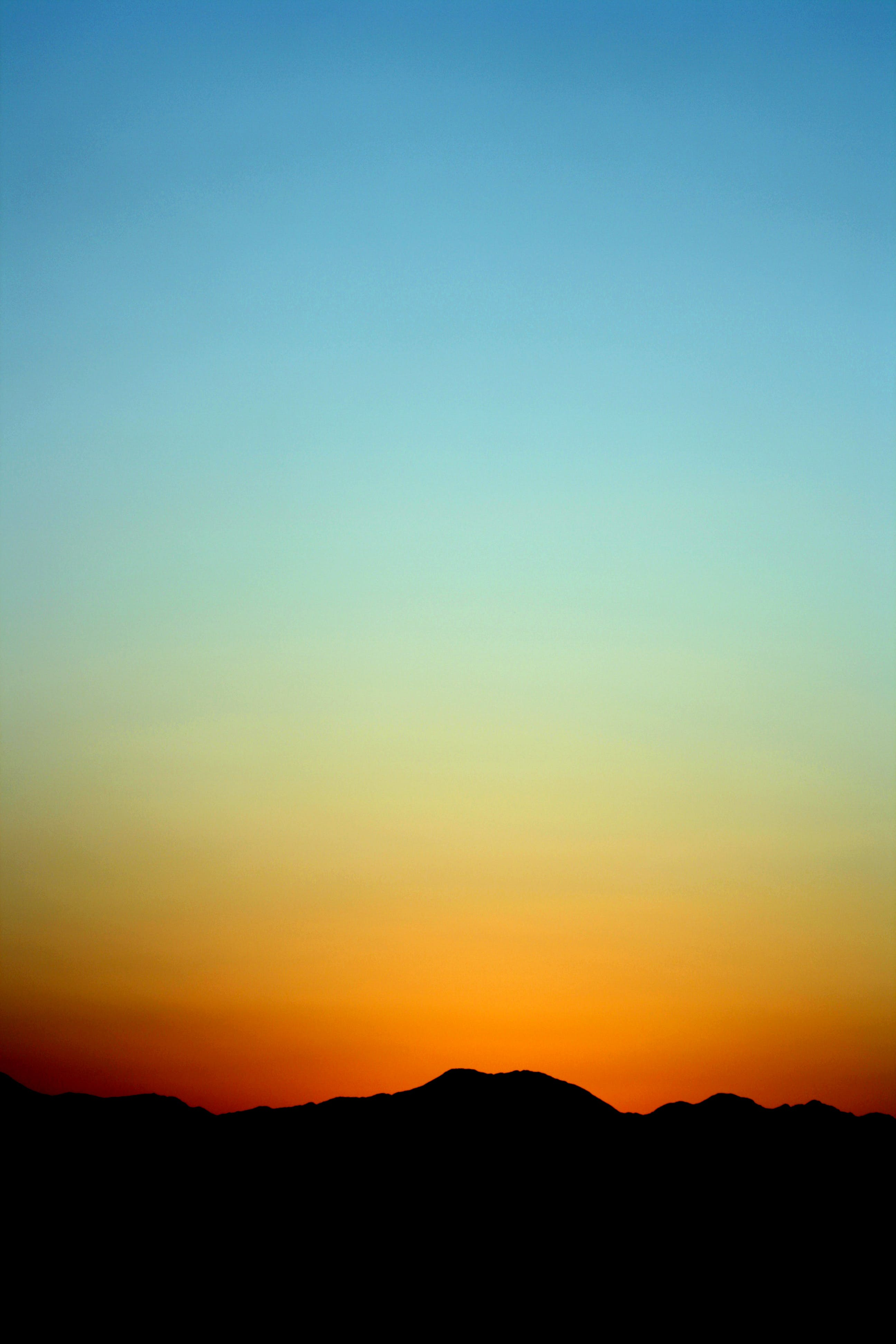 Silhouette of Mountain Under Orange and Blue Sky during Sunset